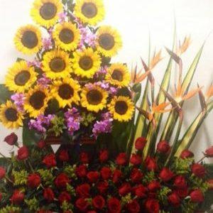 Arreglo dos pisos con girasoles , rosas rojas y orquídeas