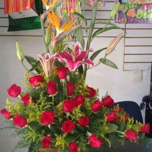 Arreglo media luna aves del paraíso , lirios y rosas rojas