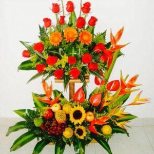 Arreglo con frutas de dos pisos con rosas rojas y flores tropicales