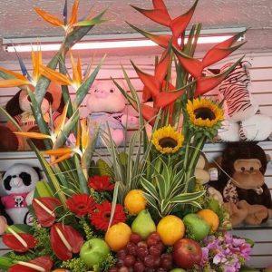 Arreglo con frutas y  flores tropicales