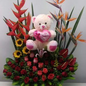 Jardinera con heliconias, aves del paraíso, peluche rosas rojas y salmón