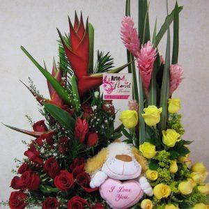 Jardinera heliconias, yinyer con peluche perro y rosas rojas